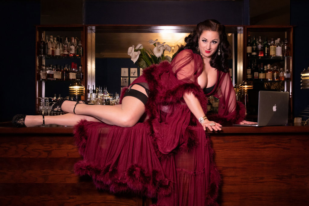 Tempest Rose, founder of House Of Burlesque, reclines at Fontaine's Bar with her laptop - 25 Blog Post Topic Ideas For Boudoir Photographers