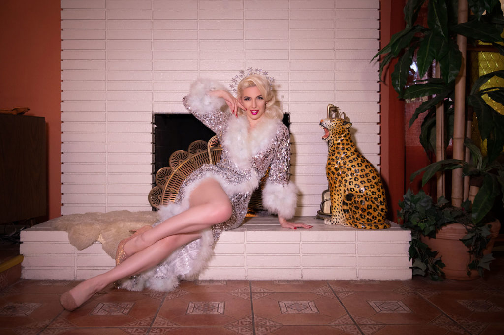 Socially Distanced Christmas - burlesque performer Miss Tosh sitting in front of the fireplace